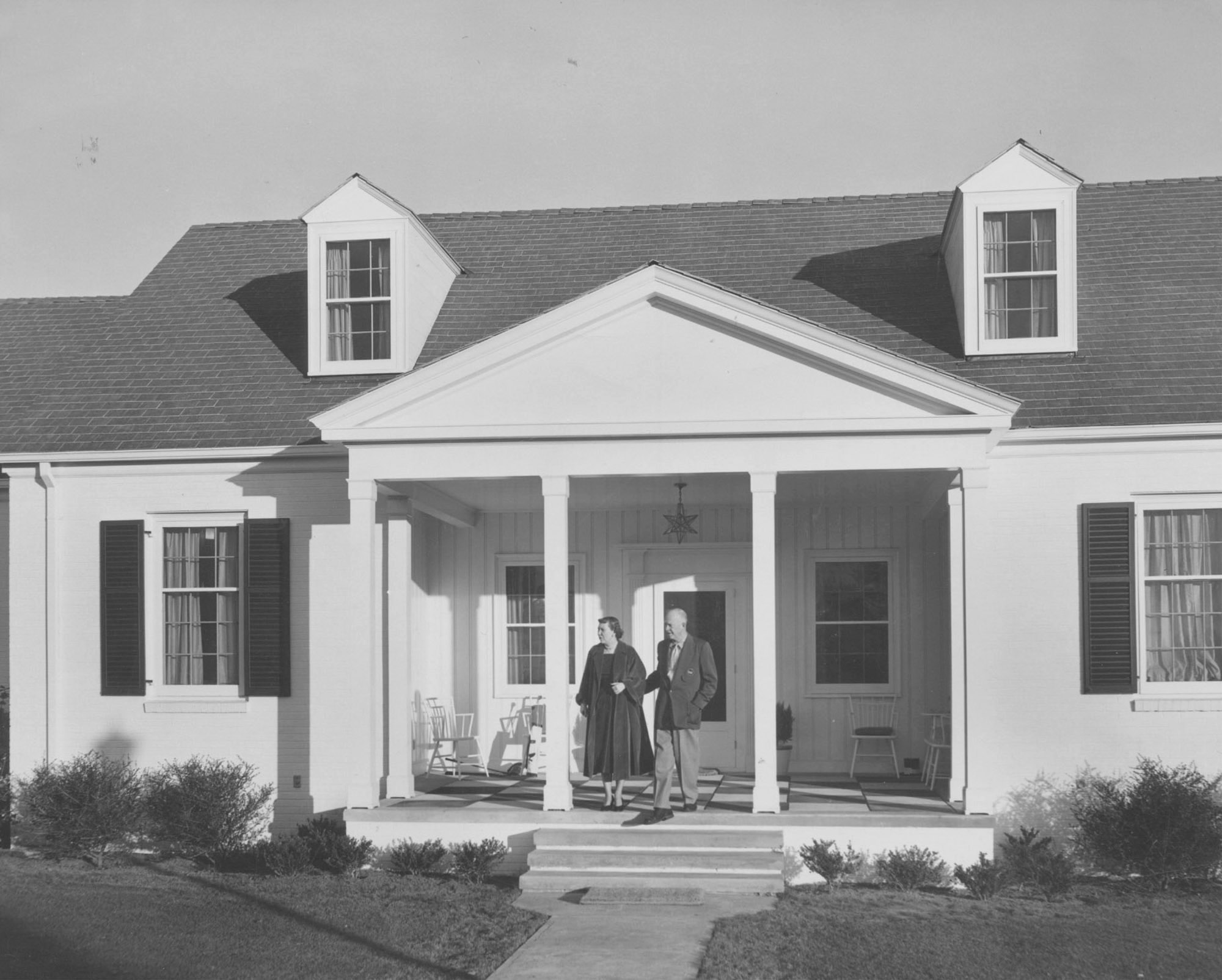 """President and Mrs. Eisenhower stand on the porch of their """"little white house"""" at the Augusta National Golf Club. [FILE]"""